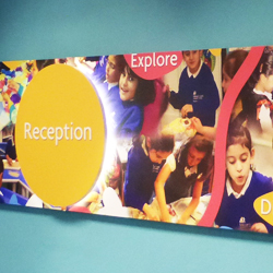 Large canvas school montage with lit up circular sign